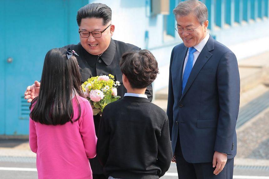 North Korean leader Kim Jong Un (left), accompanied by South Korean President Moon Jae In, receives a bouquet from South Korean children residing in a border village.