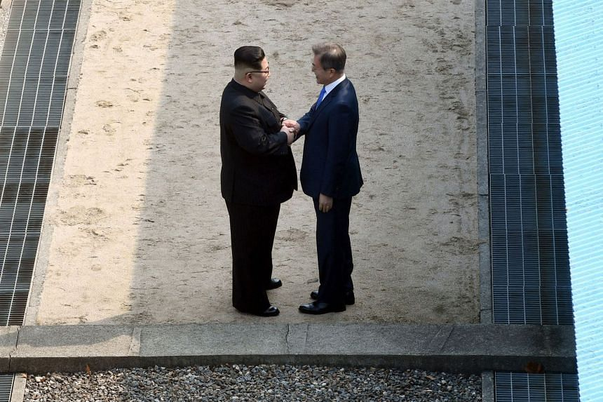 North Korea's leader Kim Jong Un (left) shakes hands with South Korea's President Moon Jae In at the Military Demarcation Line that divides their countries at Panmunjom, on April 27, 2018.