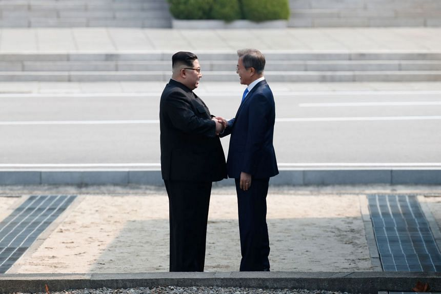 North Korea's leader Kim Jong Un (left) shakes hands with South Korea's President Moon Jae In at the Military Demarcation Line that divides their countries ahead of their summit at Panmunjom, on April 27, 2018.