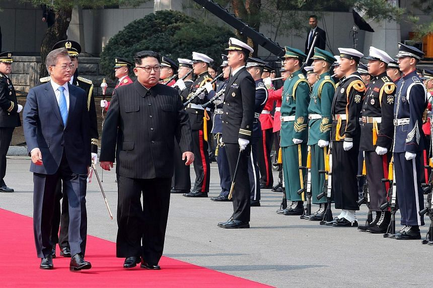 North Korea's leader Kim Jong Un (left) walks with South Korea's President Moon Jae In past a guard of honour to the official summit Peace House building at Panmunjom, on April 27, 2018.