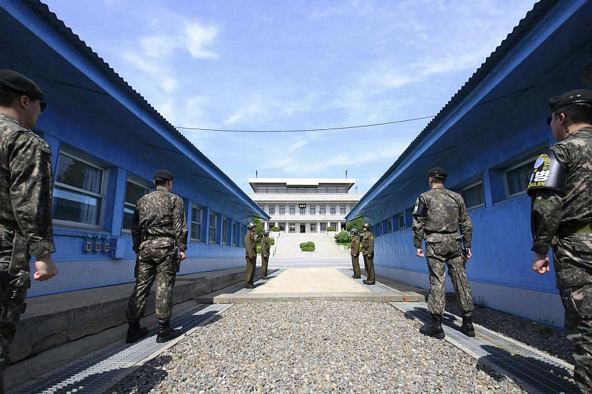 South Korean soldiers (front) and North Korean soldiers (rear) stand guard on either side of the military demarcation line of the Demilitarized Zone dividing the two nations, in Panmunjom, South Korea, on April 26, 2018.