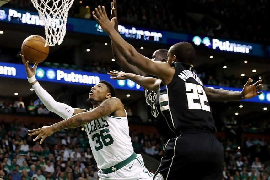 Boston, MA, USA; Boston Celtics guard Marcus Smart (36) shoots against Milwaukee Bucks forward Khris Middleton (22) during the fourth quarter of Boston's 92-87 win in game five of the first round of the 2018 NBA Playoffs at TD Garden.