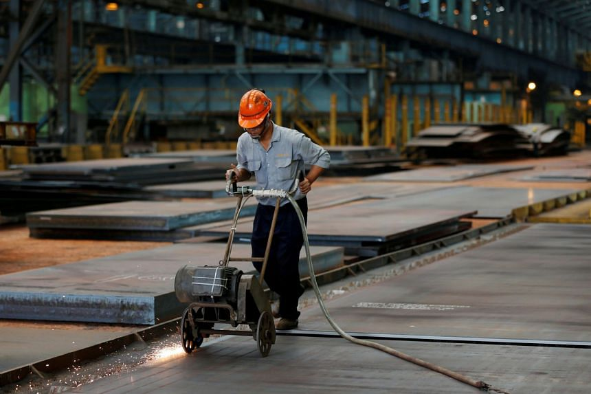 A worker cuts steel plates inside the China Steel Corporation factory, in Kaohsiung, southern Taiwan.