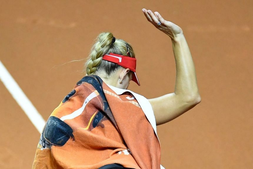 Kerber waves to spectators after she was forced to give up the match due to injury.