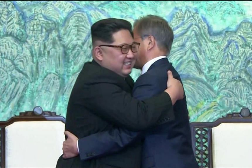 South Korean President Moon Jae In and North Korean leader Kim Jong Un embrace after signing agreements during the inter-Korea summit at Panmunjom on April 27, 2018.