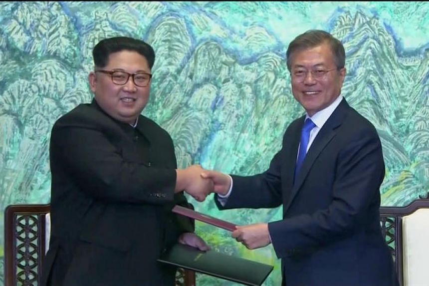 South Korean President Moon Jae In and North Korean leader Kim Jong Un shaking hands after signing agreements during the inter-Korea summit at the truce village of Panmunjom on April 27, 2018.
