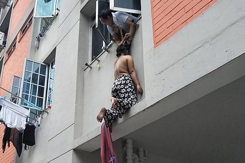 In a video that has been circulating on Facebook, the woman is seen being held by Mr Azman Jalil. In another video clip, she is seen lying at the foot of the block.