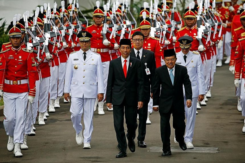 Indonesia President Joko Widodo and Vice-President Jusuf Kalla during a ceremony in Jakarta last year. Mr Joko is hard pressed to find a running mate for next year's election who has all the key qualifications that his current V-P has.