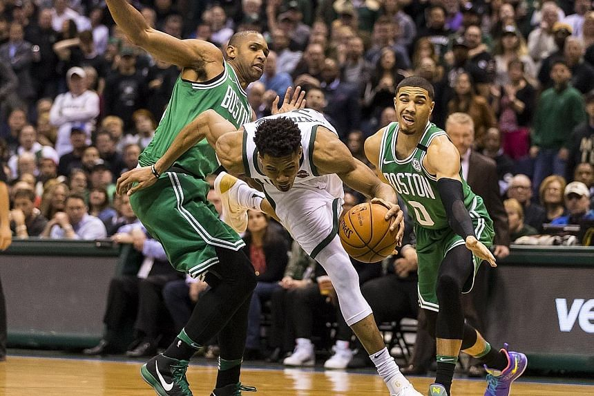 Milwaukee Bucks forward Giannis Antetokounmpo driving for the basket around Boston Celtics forward Al Horford (left), as forward Jayson Tatum fails to keep pace in Game 6 of their NBA play-offs first-round clash. The series is tied at 3-3.