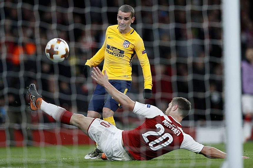 Atletico Madrid forward Antoine Griezmann evading a challenge by Arsenal defender Shkodran Mustafi's to net his 82nd-minute equaliser. The second leg will be played in Madrid next Thursday.
