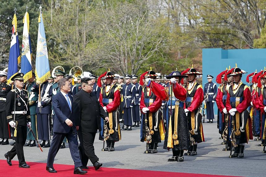 South Korean President Moon Jae In and North Korean leader Kim Jong Un inspecting the guard of honour at the Peace House in the truce village of Panmunjom in the South yesterday. Mr Moon quipped that Mr Kim could see a better performance if he visite