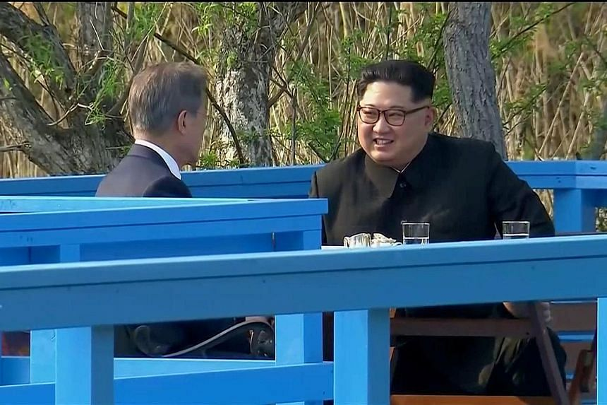 South Korean President Moon Jae In and North Korean leader Kim Jong Un having a private chat on a footbridge in the truce village of Panmunjom yesterday. North Korean leader Kim Jong Un and South Korean President Moon Jae In planting a commemorative