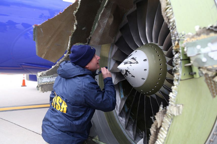 Investigators examine an engine on the Southwest Airlines flight.
