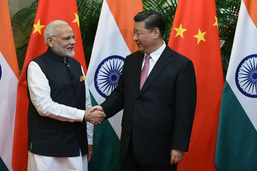 India's Prime Minister Narendra Modi (left) shaking hands with Chinese President Xi Jinping in Wuhan, on April 27, 2018.
