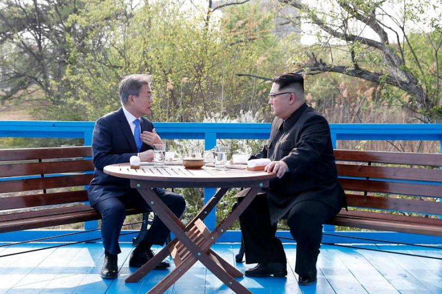 South Korean President Moon Jae In talks with North Korean leader Kim Jong Un at the end of a blue bridge in the border village of Panmunjom, South Korea, on April 27, 2018.