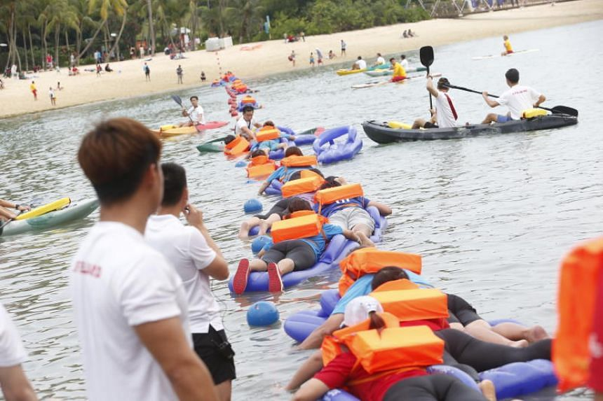 Residents participate in a record-setting activity by forming a line in the sea using slipper floats.