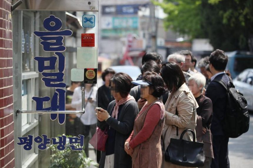 People wait in a long queue to enter a restaurant famous for Pyongyang-style cold noodles, or 'naengmyeon' in Korean, in Seoul, South Korea, on April 27, 2018.