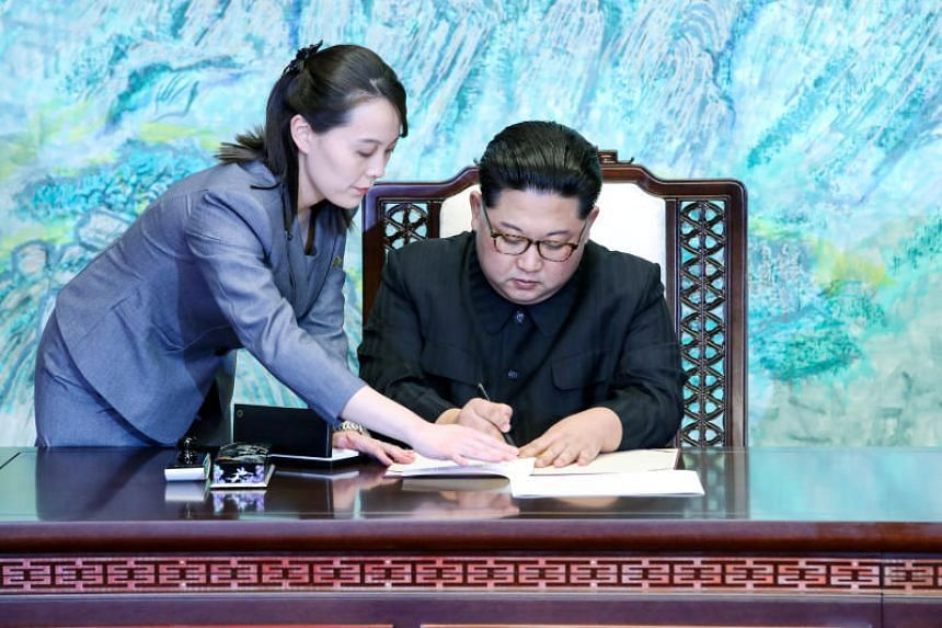 North Korean leader Kim Jong Un is assisted by his sister Kim Yo Jong as he signs documents at the truce village of Panmunjom inside the demilitarized zone separating the two Koreas in South Korea, on April 27, 2018.