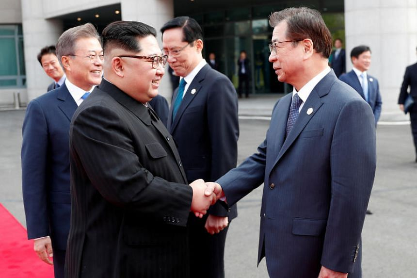 North Korean leader Kim Jong Un shakes hands with Suh Hoon, South Korea's chief of the National Intelligence Service at the truce village of Panmunjom, on April 27, 2018.