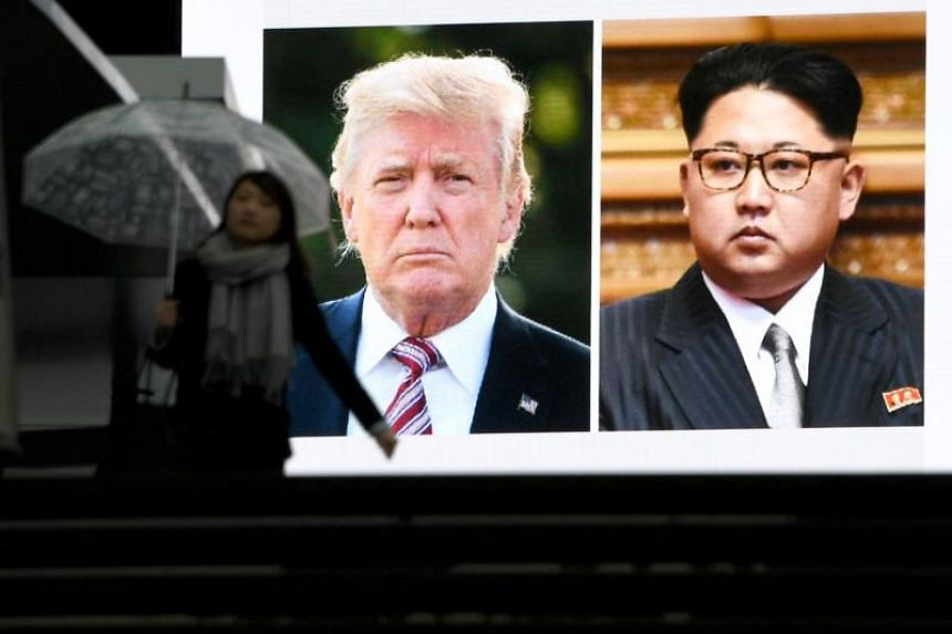 A pedestrian walks in front of a huge screen flashing a news report relating to US President Donald Trump and North Korean leader Kim Jong agreeing to meet for talks  on March 9, 2018.