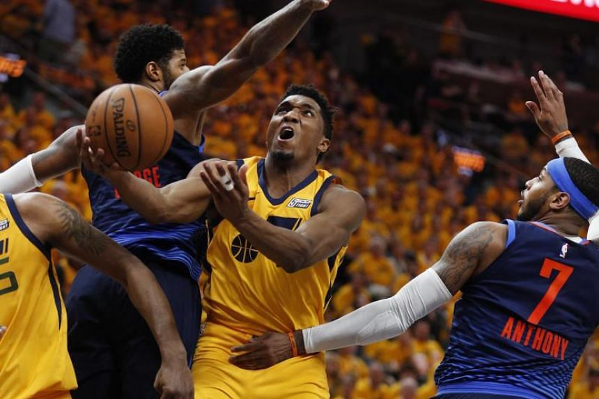 Utah Jazz guard Donovan Mitchell (centre) drives between Oklahoma City Thunder forward Paul George (left) and Oklahoma City Thunder forward Carmelo Anthony (right) in the second half during the NBA Western Conference First Round playoff game six in S