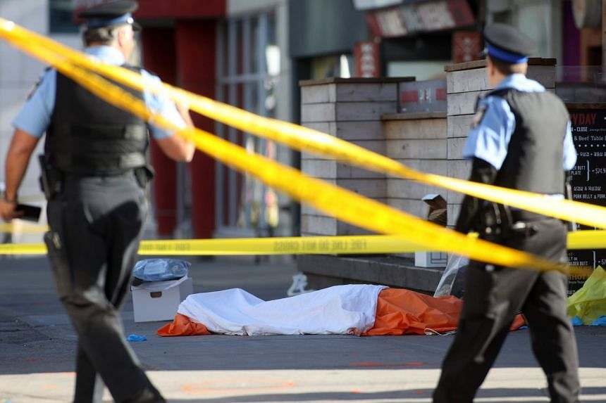 Police officers stand near one of the bodies after a truck hit pedestrians in Toronto, Canada.
