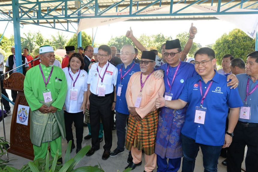 Candidates from MCA, one of the Barisan Nasional (BN) component parties, and the DAP, from the four-party opposition pact Pakatan Harapan (PH), taking a group photo.