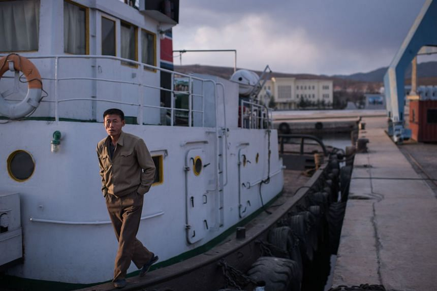 A sailor stands on his boat in a port in Rason, North Korea.