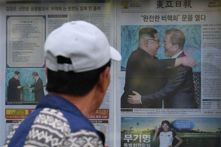 A man walks past a newspaper featuring a front page story about the summit between South Korean President Moon JaeIn and North Korean leader Kim Jong Un, on a sidewalk in Seoul, on April 28, 2018.