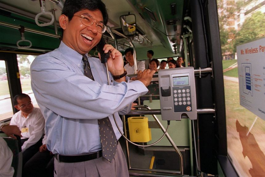 Dr Yaacob Ibrahim trying out a new phone on a Tibs bus in 1998.