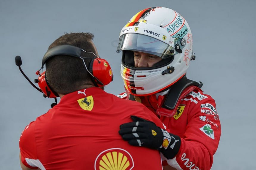 Vettel is greeted by a team member after taking the pole position.