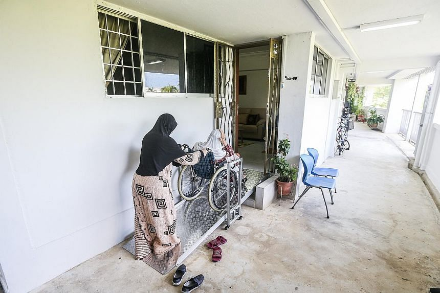 Ms Diana Norahman pushes her mother, 71, in her wheelchair up the customised fixed ramp, which was installed two weeks ago, at their HDB flat entrance. Previously, the family had one wheelchair at the bottom of the steps and another one inside the fl