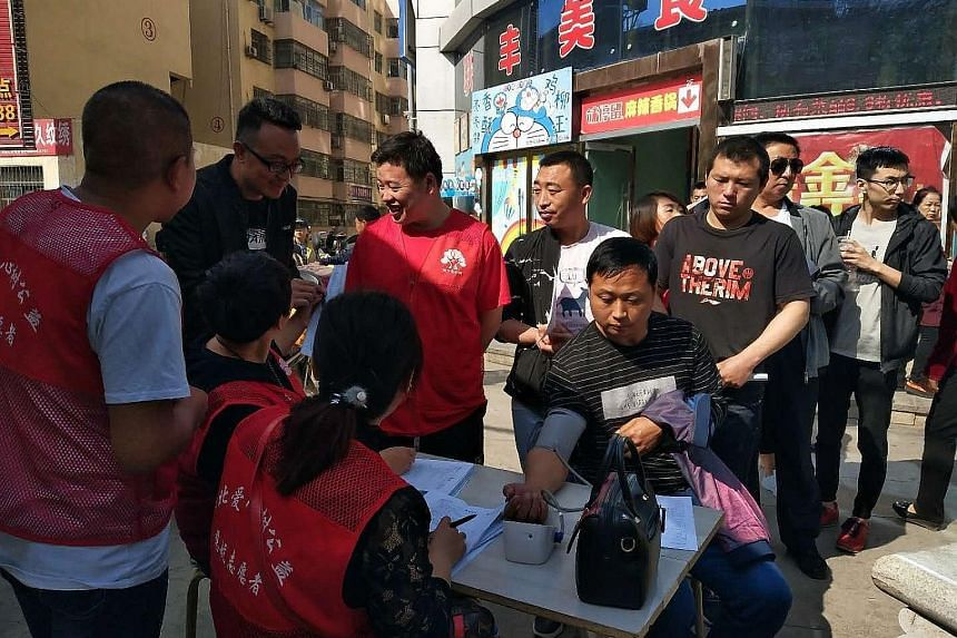 People lining up yesterday to donate blood to victims of a knife attack at a school in Mizhi county, Shaanxi province, China. Nine children were killed and 10 others hurt in Friday's incident.