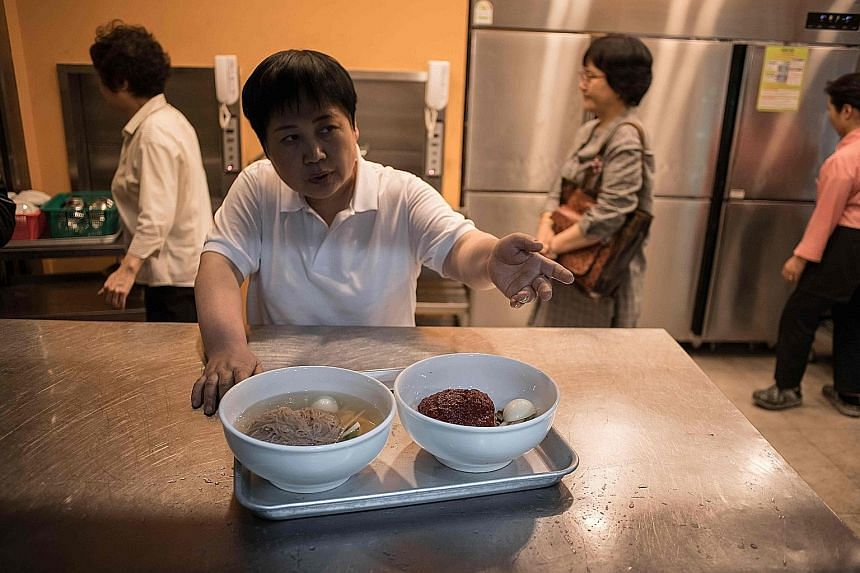 """A worker preparing to serve """"Pyongyang naengmyeon"""", a cold noodle dish, at the Nampo Myeonok noodle bar restaurant in Seoul yesterday. Demand for North Korea's signature dish peaked all over the South's capital after it was featured on the menu at th"""