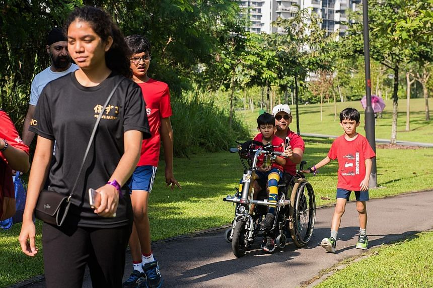 The first Special People Bi/Triathlon, organised by social enterprise The Special People and supported by the Jalan Kayu Community Sports Council, was held yesterday. Left: Former national track star K. Jayamani cheers on her foster son, 21-year-old