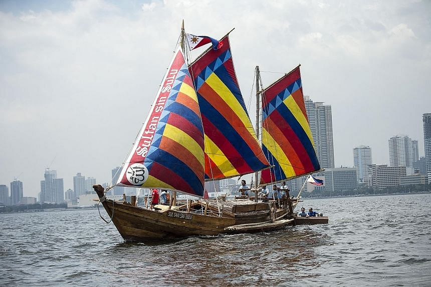 """A Filipino crew setting sail aboard the wooden boat """"Sultan Sin Sulu"""" from Manila Bay yesterday. Crafted from a centuries-old design, three identical wooden boats have set off from the Philippine capital for China to retrace a historic trip by a Fili"""