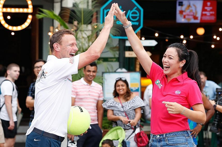 World No. 1 women's tennis doubles player Latisha Chan, high-fiving former England striker Teddy Sheringham during a cross-sports activity at Clarke Quay yesterday. Chan, 28, is in Singapore to promote the Oct 21-28 WTA Finals ahead of the ticket sal