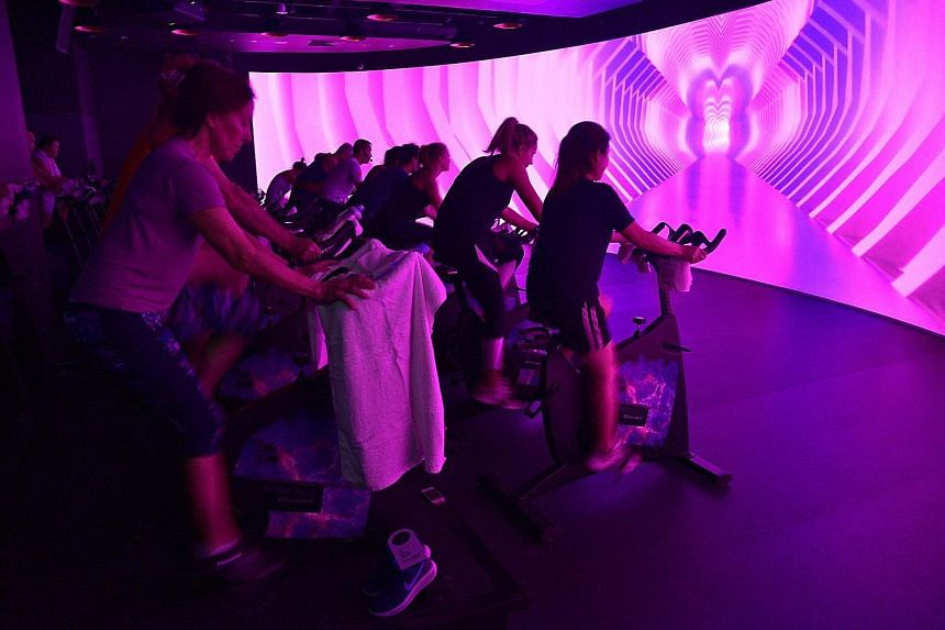 Participants getting into the groove of VR cycling, which uses technology to change the whole workout experience.