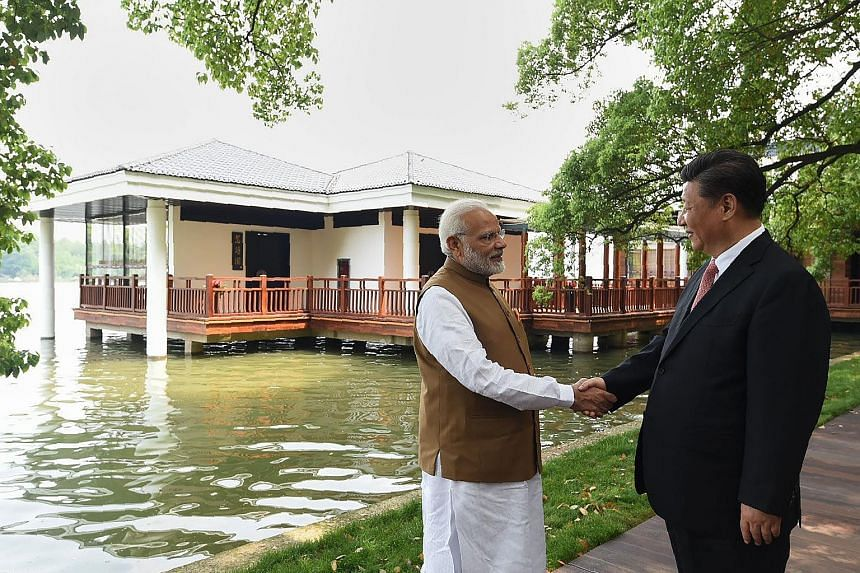 "Chinese President Xi Jinping with Indian PM Narendra Modi at Wuhan's East Lake. The two leaders issued ""strategic guidance to their respective militaries"" to strengthen communication and build trust, and both sides agreed to handle differences with m"