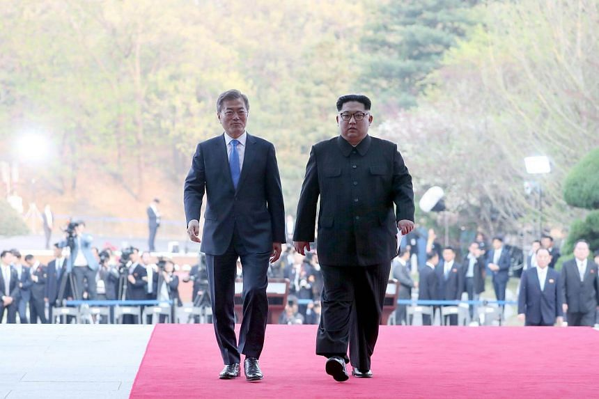 President Moon Jae In of South Korea (left) and North Korea's leader Kim Jong Un walking together during their summit at the truce village of Panmunjom on April 27, 2018.