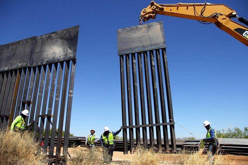 Workers replace an old section of the wall between the US and Mexico in Santa Teresa, New Mexico State, US, on April 23, 2018.