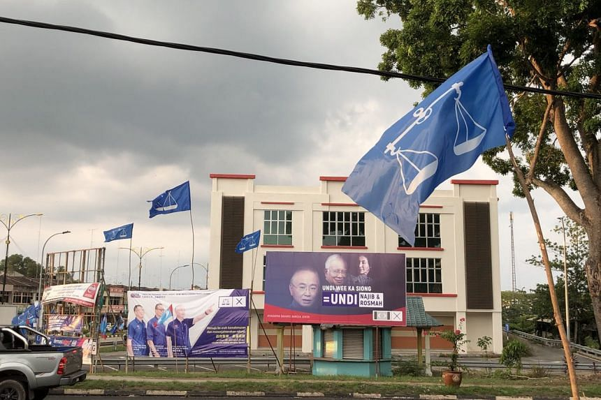 A poster put up by the opposition Pakatan Harapan featuring the images of Barisan Nasional candidate Wee Ka Siong and Malaysian PM Najib Razak and his wife Rosmah, in Yong Peng.