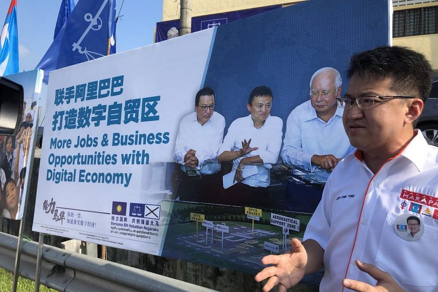 Pakatan Harapan candidate for Ayer Hitam constituency Liew Chin Tong speaking in front of a poster featuring MCA president Liow Tiong Lai, PM Najib Razak and Alibaba mogul Jack Ma.