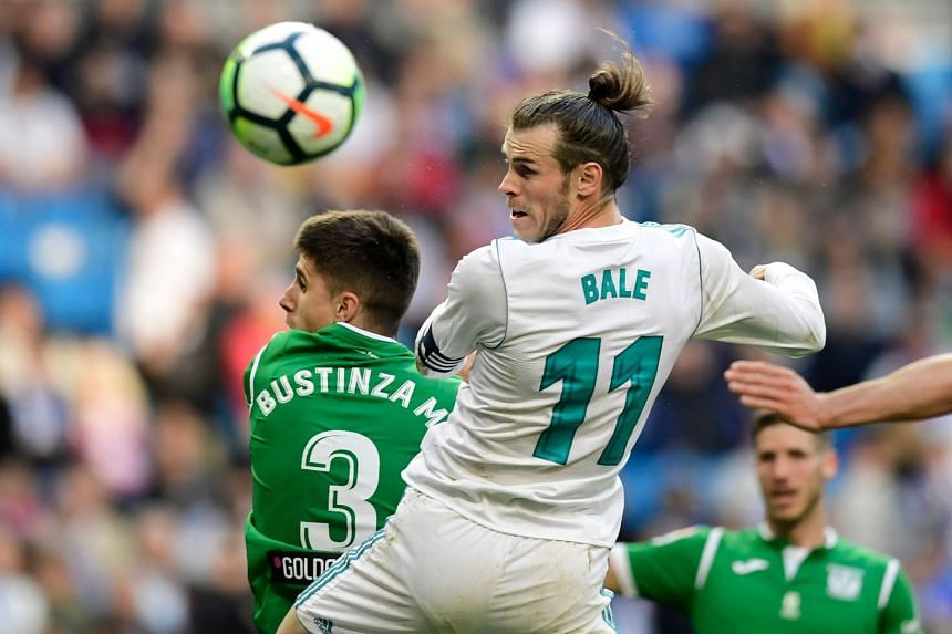 Real Madrid's Welsh forward Gareth Bale heads the ball with Leganes' Spanish defender Unai Bustinza (left).