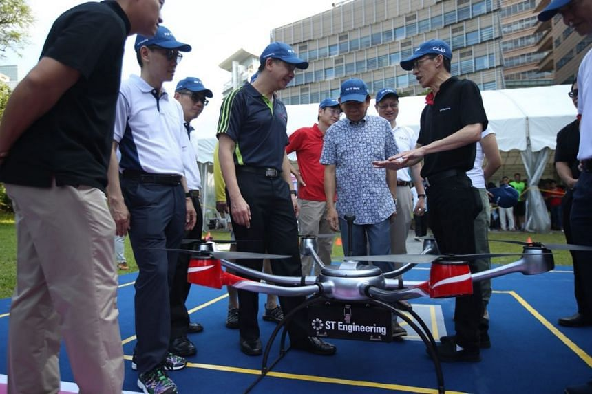 An ST Aerospace spokesman demonstrating the use of an unmanned aircraft as Transport Minister Khaw Boon Wan looks on.