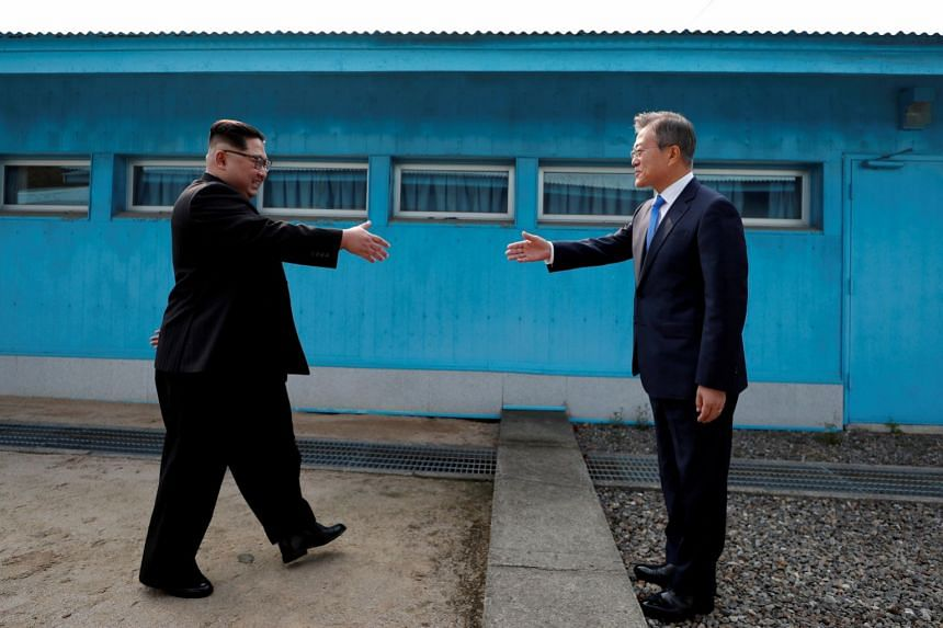 North Korea's Kim Jong-un (left) and the South's Moon Jae-in shake hands in the truce village of Panmunjom.