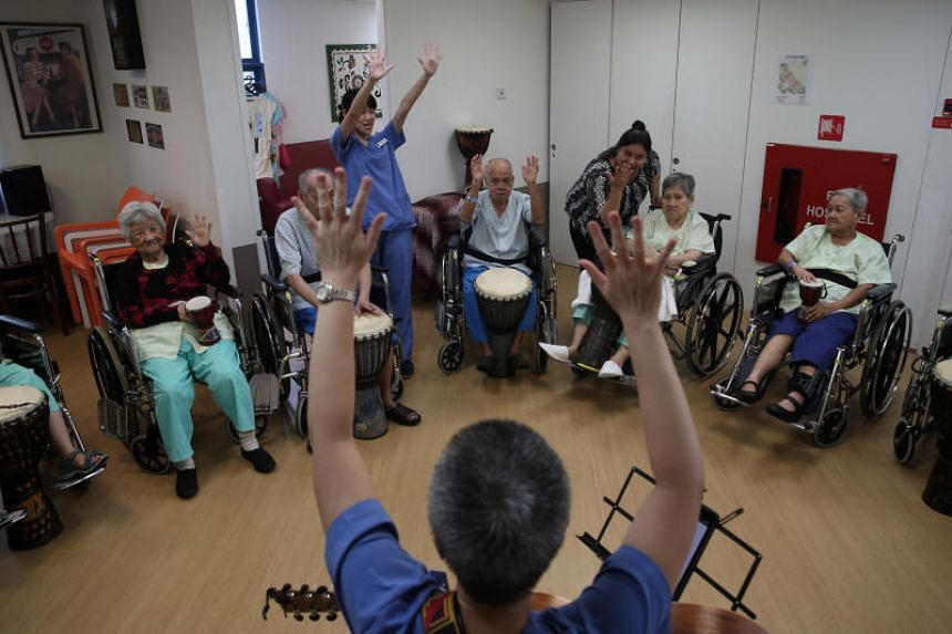 A musical therapist leading patients in a group session at St Andrew's Community Hospital.