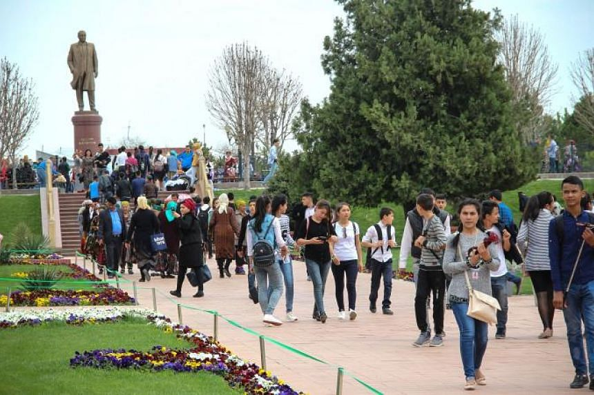 Tourists walking in front of a statue of Islam Karimov, the ruler of Uzbekistan from 1991-2016, in Samarkand on March 28, 2018.