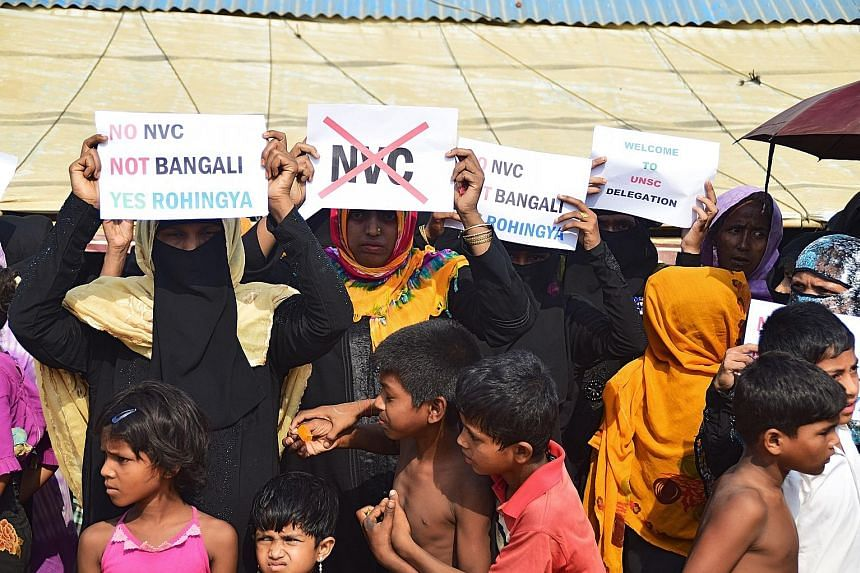 Rohingya refugees holding placards to members of the United Nations Security Council delegation during their visit to the Kutupalong refugee camp in Bangladesh's Ukhia district yesterday. The UN diplomats spoke with some of the refugees and community