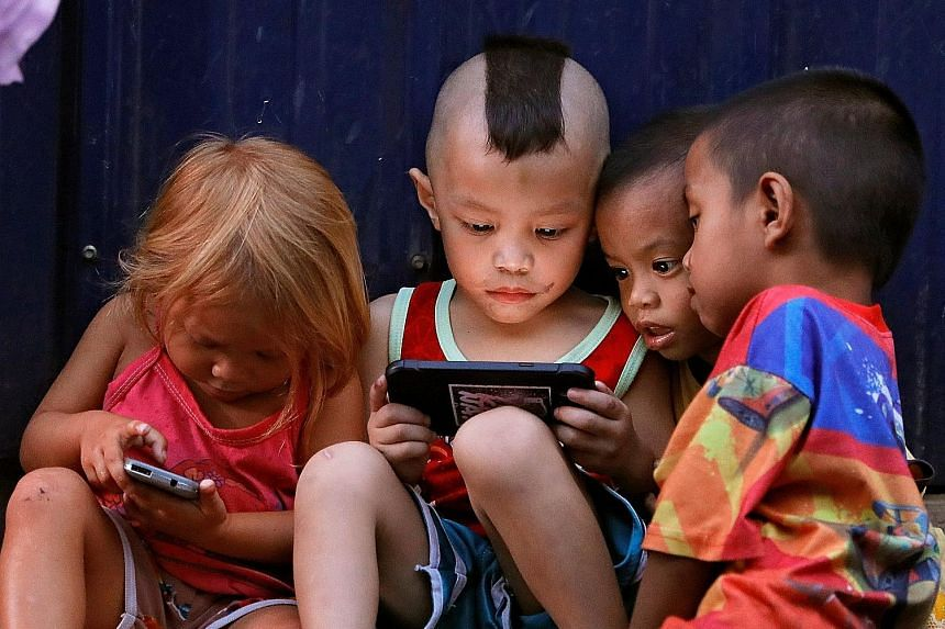 Filipino children in Cubao, Quezon City, Manila, playing games on screen devices on March 27. The use of mobile devices can cause strains from a misalignment between a student's line of sight and his hand position.